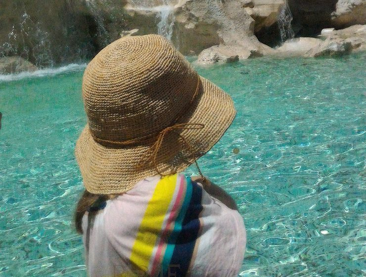 Photo of a girl throwing the coin at the Trevi Fountain during the tour